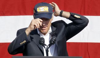 Vice President Joe Biden puts on a United Steelworkers hat before he spoke to a crowd before he joined in the annual Labor Day parade on Monday, Sept. 7, 2015, in Pittsburgh. (AP Photo/Keith Srakocic)