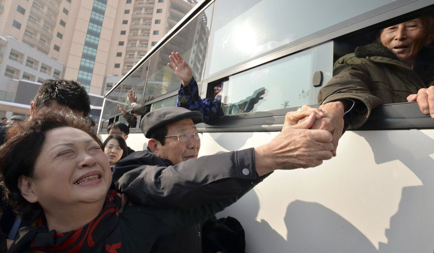 South Korean Nam Gung Bong-ja (left) cries as she holds the hand of her North Korean father Nam Gung Ryuck on a bus after a separated family reunion meeting at Diamond Mountain in North Korea on Feb. 25, 2014. The participants had only three days to meet with relatives most of them hadn't seen since the Korean War ended in an armistice in 1953. (Associated Press)