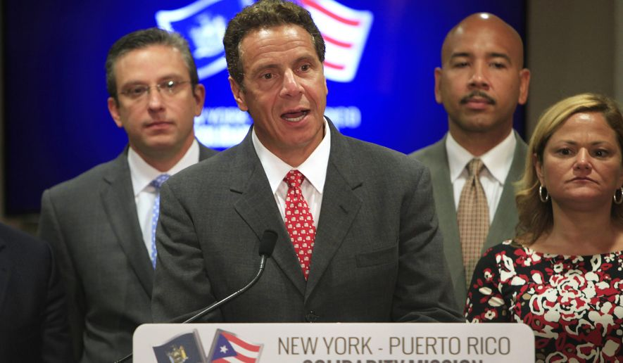 New York Gov. Andrew Cuomo speaks during a news conference in San Juan, Puerto Rico, Tuesday, Sept. 8, 2015. Cuomo and a delegation of top state officials met with Puerto Rico's Gov. Alejandro Garcia Padilla, pictured left, on Tuesday to develop what he called a historic partnership with the U.S. territory to help it emerge from a deepening economic crisis. (AP Photo/Ricardo Arduengo)