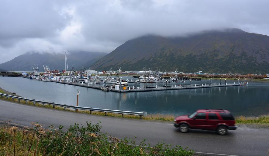 In this photo taken Sept. 23, 2013, a driver passes the small boat harbor in King Cove, Alaska.  A federal judge in Alaska on Tuesday, Sept. 8, 2015, dismissed a lawsuit brought over the U.S. Interior Department's refusal to allow for a road from King Cove to an all-weather airport at Cold Bay. The road has drawn opposition from environmental groups because it would run through Izembek National Wildlife Refuge.  (James Brooks(/Kodiak Daily Mirror via AP) MANDATORY CREDIT