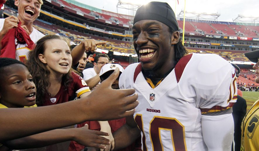 FILE - In This Aug. 25, 2012, file photo, Washington Redskins quarterback Robert Griffin III smiles as he greets fans after an NFL preseason football game against the Indianapolis Colts in Landover, Md. Griffin and Indianapolis Colts quarterback Andrew Luck were drafted back-to-back as No. 1 and 2. (AP Photo/Alex Brandon, File)
