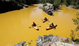 People kayak in the Animas River near Durango, Colo., in water colored with millions of gallons of mine waste into Cement Creek, which flows into the Animas River, on Aug. 6, 2015. (Jerry McBride/The Durango Herald via AP) **FILE**