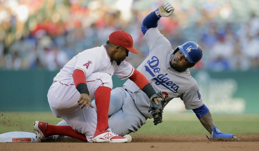 Los Angeles Dodgers' Carl Crawford, right, steals second base against Los Angeles Angels shortstop Erick Aybar during the first inning of a baseball game Monday, Sept. 7, 2015, in Anaheim, Calif. (AP Photo/Jae C. Hong)