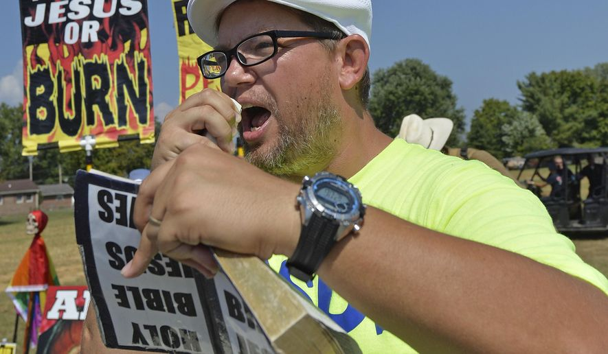 John Williams, of Cincinnati, reads from the bible to a gathering in support of jailed county clerk Kim Davis at the Carter County Detention Center in Grayson, Ky., Tuesday, Sept. 8, 2015. After five days behind bars, Davis was ordered released from jail Tuesday by the judge who locked her up for refusing to issue marriage licenses to gay couples. (AP Photo/Timothy D. Easley)