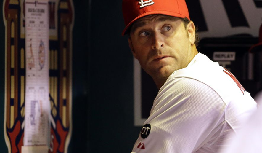St. Louis Cardinals manager Mike Matheny looks over his shoulder toward the field after looking at a line-up card taped to the dugout wall during the fourth inning of the Cardinals' baseball game against the Chicago Cubs on Tuesday, Sept. 8, 2015, in St. Louis. (AP Photo/Jeff Roberson)