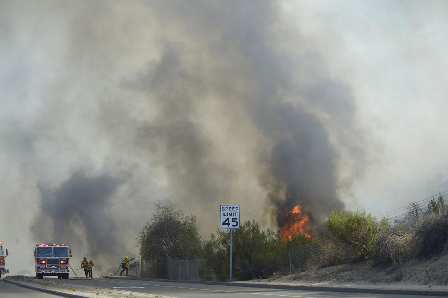 Firefighters battle a brush fire in La Habra, Calif., Tuesday, Sept. 8, 2015. (Jeff Grtichen/The Orange County Register via AP)   MAGS OUT; LOS ANGELES TIMES OUT; MANDATORY CREDIT