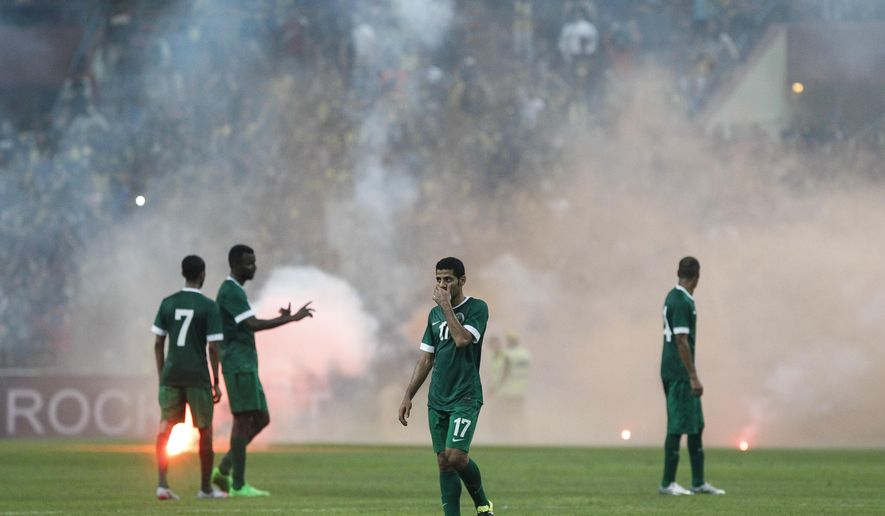 Saudi Arabia's players walk off the field after flares are thrown onto the pitch during their Group A FIFA World Cup 2018 qualifying soccer match against Malaysia in Shah Alam, Malaysia, on Tuesday, Sept. 8, 2015. (AP Photo/Joshua Paul)