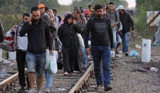 Refugees walk along the railway tracks that connect Horgos and Szeged near the Hungary-Serbia border Tuesday. President Obama says the U.S. must do more to help the issue of Syrian refugees, but both Democrats and Republicans say he has been slow to act. (Associated Press)