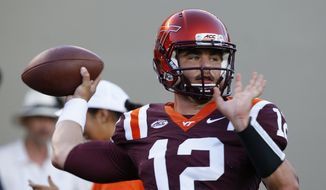 Virginia Tech quarterback Michael Brewer (12) warms up before an NCAA college football game against Ohio State in Blacksburg, Va., Monday, Sept. 7, 2015. (AP Photo/Steve Helber)