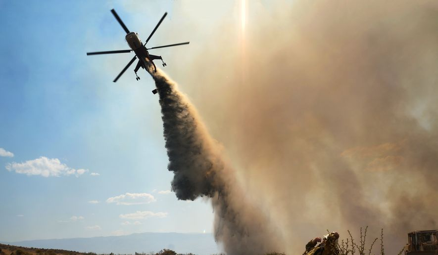 This Aug. 9, 2015, photo taken by Utah state firefighter Eli Peterson shows a firefighter watching as a helicopter makes a water drop over a fire in Owyhee County, Idaho. (Eli Peterson via AP) ** FILE **