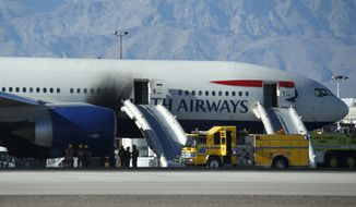 Firefighters stand by a plane that caught fire at McCarran International Airport on Tuesday in Las Vegas. An engine on the British Airways plane caught fire before takeoff, forcing passengers to escape on emergency slides. (Associated Press)