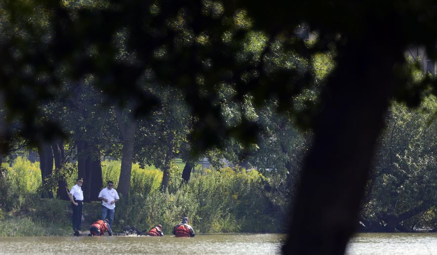 Chicago Police Marine Unit divers search a lagoon at Garfield Park, Sunday, Sept. 6, 2015, in Chicago, after a toddler's decomposed feet and hand were found on Saturday. (AP Photo/Paul Beaty)