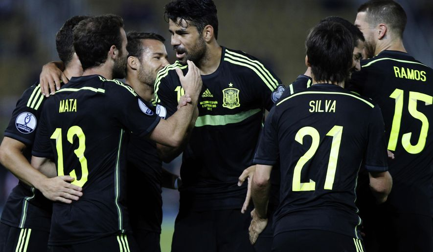 Spain's Juan Mata, left, is congratulated by his teammates after scoring the opening goal against Macedonia during the Euro 2016 qualifying match between Macedonia and Spain at the Philip II stadium, in Skopje, Tuesday, Sept. 8, 2015. (AP Photo/Vlatko Perkovski)