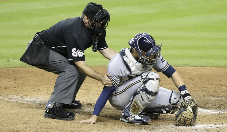 Home plate umpire David Rackley (86) helps Milwaukee Brewers catcher Jonathan Lucroy up after a foul tip hit Lucroy during the seventh inning of a baseball game against the Miami Marlins, Tuesday, Sept. 8, 2015, in Miami. The Marlins defeated the Brewers 6-4. (AP Photo/Wilfredo Lee)