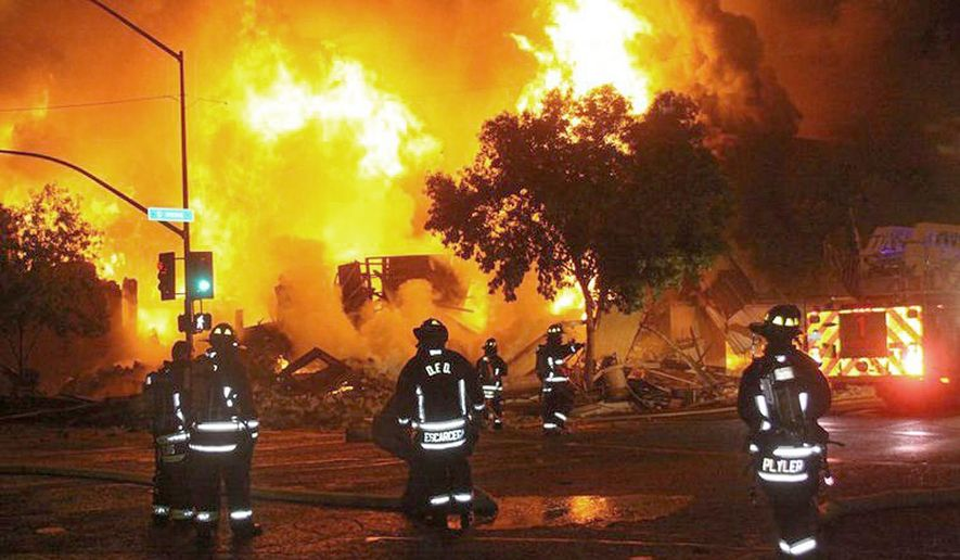 Firefighters stand outside a two-story building fully engulfed by a fire in downtown Douglas, Ariz., early Wednesday morning, Sept. 9, 2015. Arizona Public Service Co. says the commercial building fire knocked out electrical power to 7,500 APS customers in the southeastern Arizona city. (Bruce Whetten/Douglas Daily Dispatch via AP) MANDATORY CREDIT