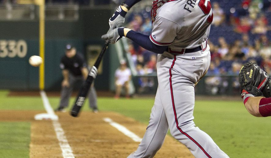 Atlanta Braves' Freddie Freeman (5) singles to right field, driving in Michael Bourn and Nick Markakis during the fourth inning of a baseball game against the Philadelphia Phillies, Wednesday, Sept. 9, 2015, in Philadelphia. (AP Photo/Laurence Kesterson)