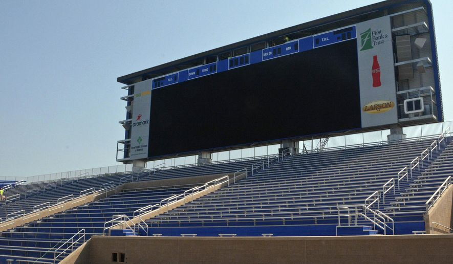 In this Aug. 26, 2015 photo, workers put finishing touches on a new jumbo video scoreboard and student section seating at Coughlin-Alumni Stadium on the South Dakota State campus in Brookings S.D. Many features of the ongoing renovation project will debut for the 2015 season as the school prepares to debut its new Dana J. Dykhouse Stadium the following year. (AP Photo/Dirk Lammers)