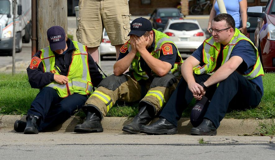 A firefighter puts his head in his hands as he and other firefighters sit on the curb on Cedar Street just north of Jolly Road Wednesday, Sept. 9, 2015 in Lansing, Mich. Dennis Rodeman, a 35-year-old Lansing firefighter has died after being struck by a hit-and-run driver as he collected money for charity. (Dave Wasinger/Lansing State Journal via AP)  NO SALES; MANDATORY CREDIT