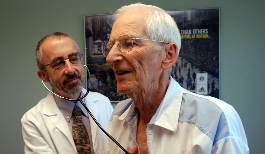 Dr. Bruce Stowell examines patient Robert Busch at his office in Grants Pass, Ore. (AP Photo/Jeff Barnard, File)