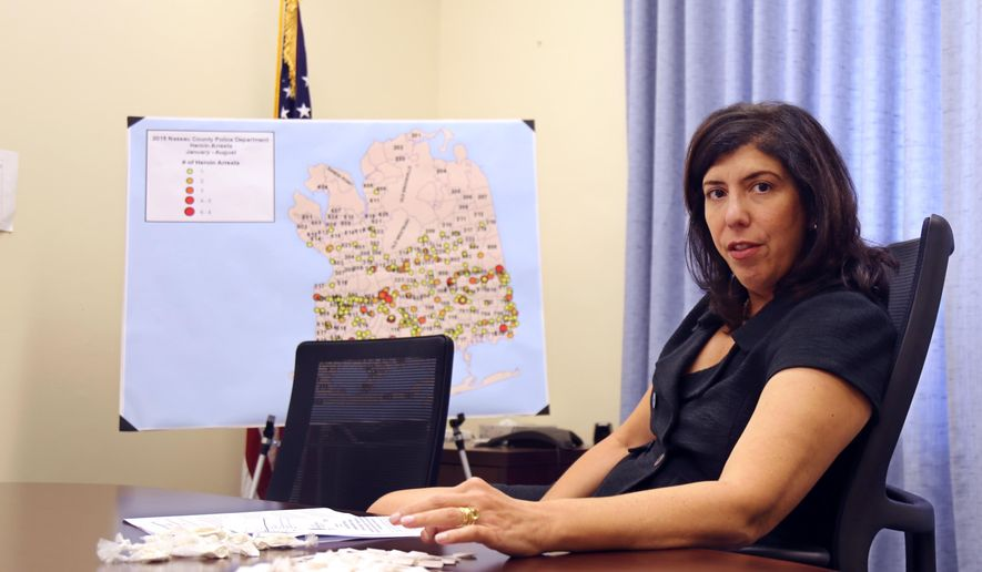 Acting Nassau County District Attorney Madeline Singas motions over packets of heroin piled on her desk, Wednesday, Sept. 9, 2015, in Mineola, N.Y. Aiming to curb rising heroin use in the suburbs of New York City, prosecutors on Long Island have written legislation that would allow authorities to charge heroin dealers with homicide after fatal overdoses. (AP Photo/Mike Balsamo)