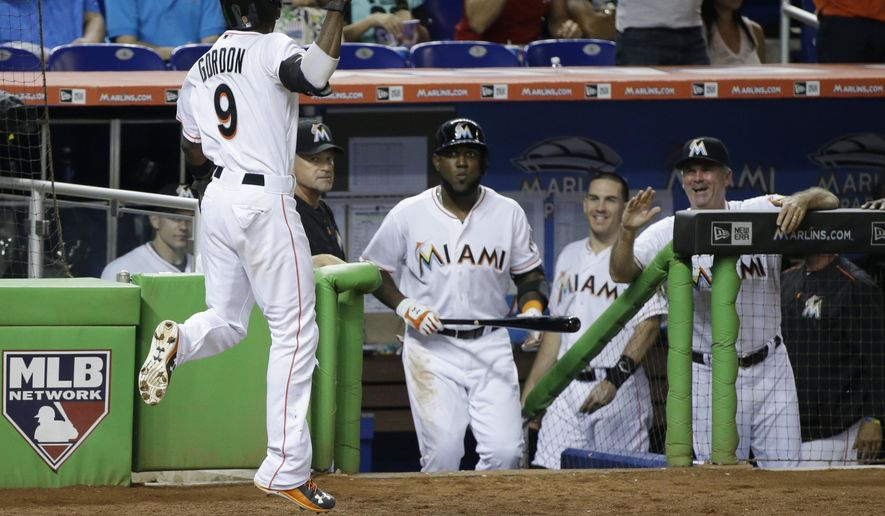 Miami Marlins' Dee Gordon (9) jumps as he celebrates after he and Tom Koehler scored on a single by Martin Prado, during the third inning of a baseball game against the Milwaukee Brewers, Wednesday, Sept. 9, 2015, in Miami. (AP Photo/Wilfredo Lee)