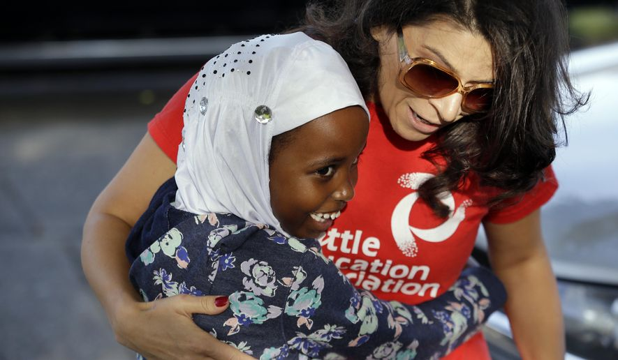 First grade student Halima Said, 6, meets her new teacher, Amber Simonton, for the first time on the picket line where Simonton joined other teachers Wednesday morning, Sept. 9, 2015, in Seattle. Teachers in Seattle began walking picket lines Wednesday after last-minute negotiations over wages and other issues failed to avert a strike in Washington state's largest school district. Classes for 53,000 Seattle Public Schools students were canceled Wednesday, on the scheduled first day of school. (AP Photo/Elaine Thompson)