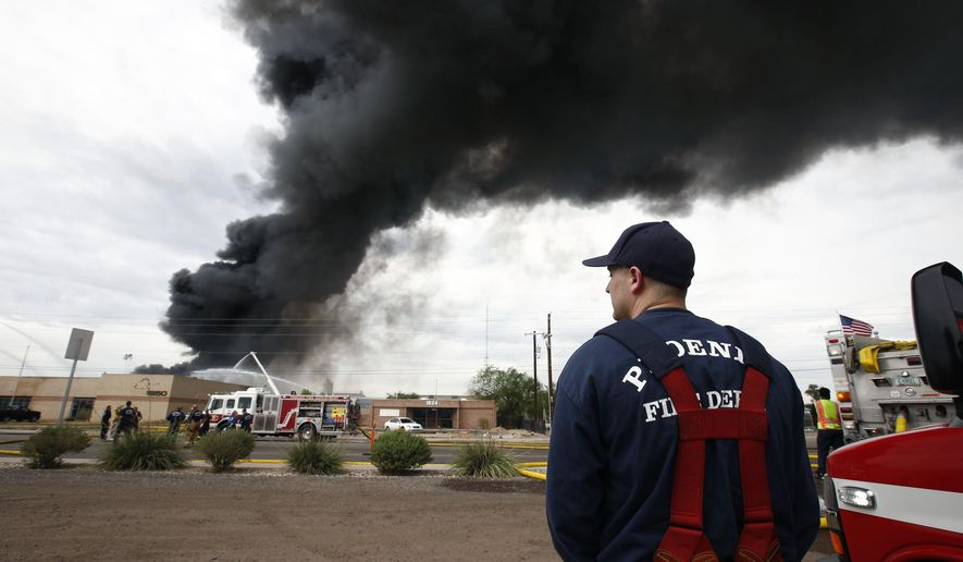 Firefighters battle a three-alarm hazmat fire at 1850 W. Broadway, Wednesday, Sept. 9, 2015 in Phoenix. Firefighters have gained control over a three-alarm hazmat fire at a solvent recycling company that blackened the sky south of downtown Phoenix for more than an hour. (Rob Schumacher/The Arizona Republic via AP)  MARICOPA COUNTY OUT; MAGS OUT; NO SALES; MANDATORY CREDIT