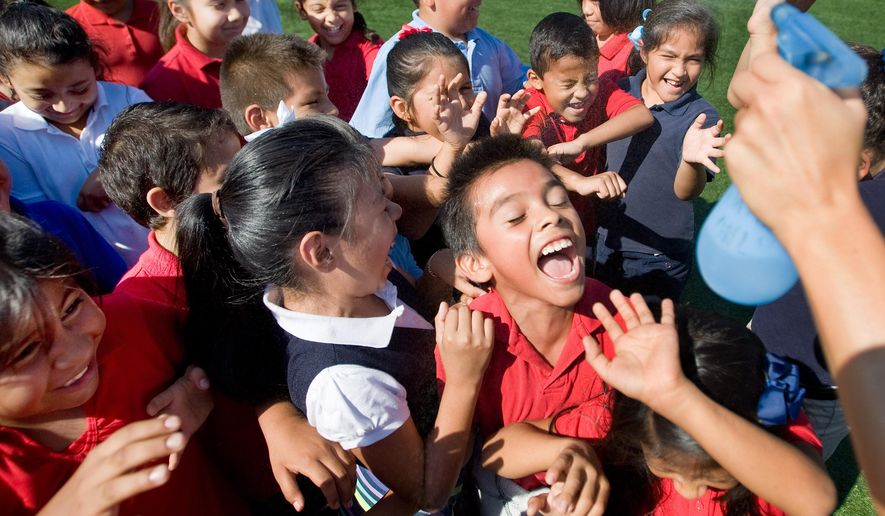 Students enjoy a cool spray of water while on the playground with classmates at Garfield Elementary School in Santa Ana, Calif. on Wednesday, Sept. 9, 2015. (Mindy Schauer/The Orange County Register via AP)   MAGS OUT; LOS ANGELES TIMES OUT; MANDATORY CREDIT