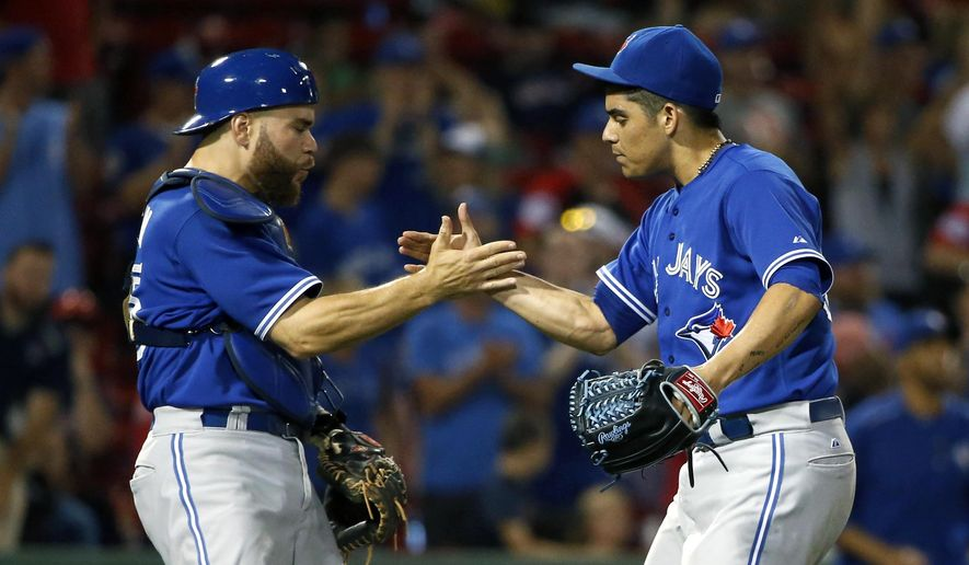 Toronto Blue Jays' Roberto Osuna, right, and Russell Martin celebrate after the Blue Jays defeated the Boston Red Sox 5-1 in 10 innings during a baseball game in Boston, Tuesday, Sept. 8, 2015. (AP Photo/Michael Dwyer)