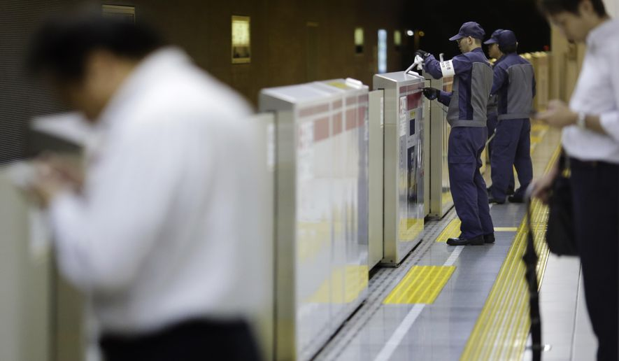 Workers check the half-height platform screen doors at a subway station platform in Tokyo Thursday, Sept. 10, 2015. Japan launched suicide prevention week on Thursday, part of a global World Health Organization effort marking Sept. 10 as World Suicide Prevention Day. (AP Photo/Eugene Hoshiko)