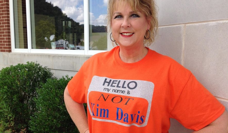 Kim Tabor, a clerk at the judicial center in Morehead, KY., wears a T-shirt to work claiming she is not Kim Davis, the  Rowan County clerk, Wednesday Sept. 9, 2015. Tabor, who works across the street from Davis, had the T-shirt made after people confusing her office with Davis' would enter the building and start screaming at her. According to Tabor, the bright orange T-shirt breaks the tension and lightens the mood of those than come into the judicial center. (AP Photo/ Dylan T. Lovan)