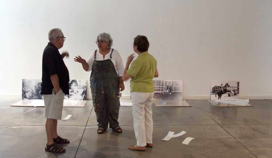 Viola Delgado, center, who's curating the exhibit, speaks with Albert Valtierra and Rosemary Hinojosa, at the Latino Cultural Center while working on the show that'll open there on September 11th, in Dallas on Saturday, Sept. 5, 2015. (Guy Reynolds/The Dallas Morning News via AP) MANDATORY CREDIT; MAGS OUT; TV OUT; INTERNET USE BY AP MEMBERS ONLY; NO SALES