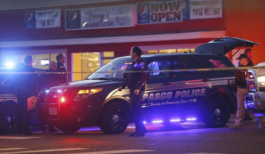 FILE - In this Feb. 10, 2015, file photo, Pasco Police officers investigate the scene of the shooting of Antonio Zambrano-Montes, who was shot by police in Pasco, Wash. A prosecutor says three police officers in Washington state who fatally shot a rock-throwing Mexican immigrant in February will not face criminal charges, Wednesday, Sept. 9, 2015 (Andrew Jansen/Tri-City Herald via AP, File)