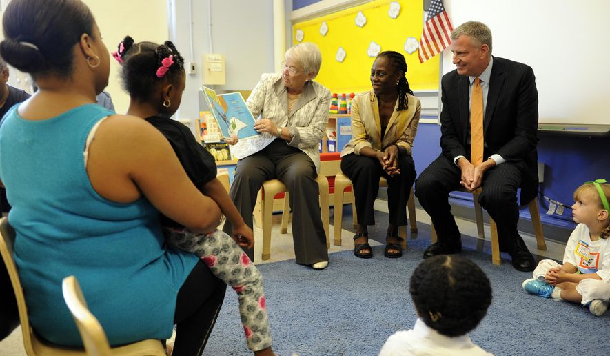 New York City Schools Chancellor Carmen Farina, left, reads a book to first time teacher Paige Buono's class as first lady Chirlane McCray, and Mayor Bill de Blasion look on during the first day of school at PS 59  Wednesday, Sept. 9, 2015, in Staten Island, N.Y. Mayor de Blasio is kicking off the school year with visits to schools in all five boroughs. (Barry Williams/New York Daily News via AP, Pool)