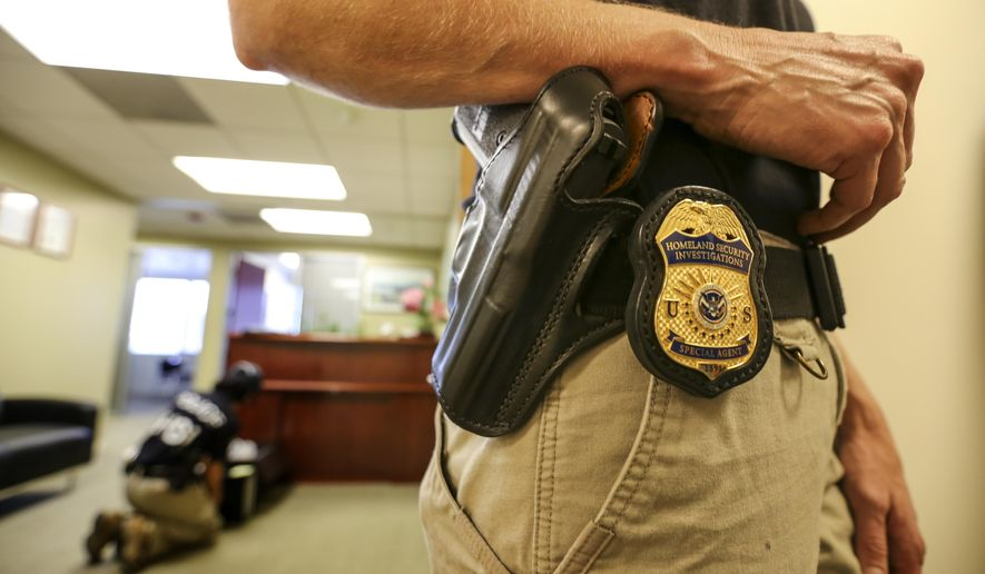 An Immigration and Customs Enforcement agent stands by as they raid an office, Wednesday, Sept. 9, 2015 in Pasadena, Calif. According to authorities, 3 people earned millions by arranging sham marriages to help get a US residency. (Irfan Khan/Los Angeles Times via AP) MANDATORY CREDIT NO FORNS; NO SALES; MAGS OUT; ORANGE COUNTY REGISTER OUT; LOS ANGELES DAILY NEWS OUT; INLAND VALLEY DAILY BULLETIN OUT; TV OUT