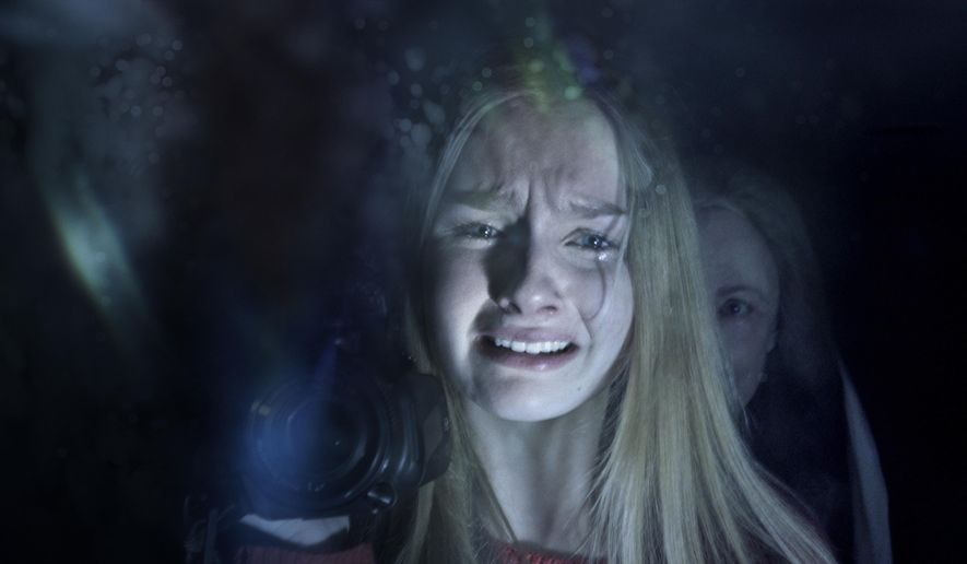 "In this image released by Universal Pictures, Olivia DeJonge, foreground, and Deanna Dunagan appear in a scene from ""The Visit."" (Universal Pictures via AP)"