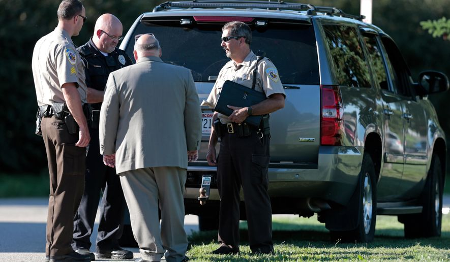 DeForest police and Dane County sheriff's deputies talk outside Yahara Elementary School in DeForest, Wis., Wednesday, Sept. 9, 2015. The Wisconsin school district says police have found nothing as they search an elementary school where someone reported a man with a gun. (Michael P. King/Wisconsin State Journal via AP) MANDATORY CREDIT