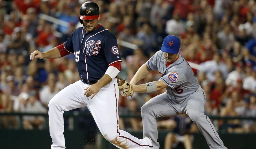 Washington Nationals' Clint Robinson (25) is out on the tag by New York Mets third baseman David Wright (5) as Robinson comes off the bag during the fourth inning of a baseball game at Nationals Park, Wednesday, Sept. 9, 2015, in Washington. (AP Photo/Alex Brandon)