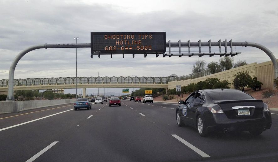 A freeway sign asked for information on on Wednesday, Sept. 9, 2015 about a shooting that shattered a rear window of a white truck on I-10 between 43rd Ave. and 35th Ave. in Phoenix earlier today. (AP Photo/Traci Carl)