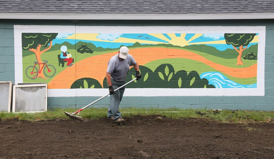 In this photo taken Wednesday, Sept. 9, 2015,  a workers prepares Riverview Launch for the grand opening. in Kalamazoo Mich. A grand opening for Riverview Launch, a former tax-foreclosed greenhouse property along the Kalamazoo River that has been redeveloped for public use, will be held Thursday, Sept. 10. (Mark Bugnaski/Kalamazoo Gazette-MLive Media Group via AP) ALL LOCAL TELEVISION OUT; LOCAL TELEVISION INTERNET OUT; MANDATORY CREDIT