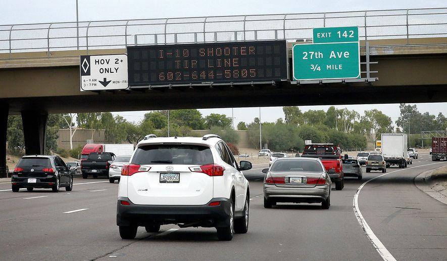 A tip line for motorist is seen on a freeway sign along I-10, Thursday, Sept. 10, 2015 in Phoenix. Numerous shootings of vehicles along I-10 over the past two weeks have investigators working around the clock to find a suspect in a spate of recent Phoenix freeway shootings that have rattled nerves and heightened fears of a possible serial shooter. (AP Photo/Matt York)