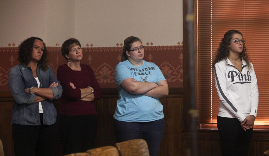 Friends and family of Jodi Parrack stand in the back of the room as Michigan State Police and St. Joseph County Prosecutor John McDonough hold a press conference to discuss the 2007 homicide of the 11-year-old girl, in Centreville, Mich., Thursday, Sept. 10, 2015. An arrest has been made in the cold case slaying of Jodi, whose body was found nearly eight years ago in a southwestern Michigan cemetery.  (Daytona Niles/Kalamazoo Gazette-MLive Media Group via AP) ALL LOCAL TELEVISION OUT; LOCAL TELEVISION INTERNET OUT; MANDATORY CREDIT