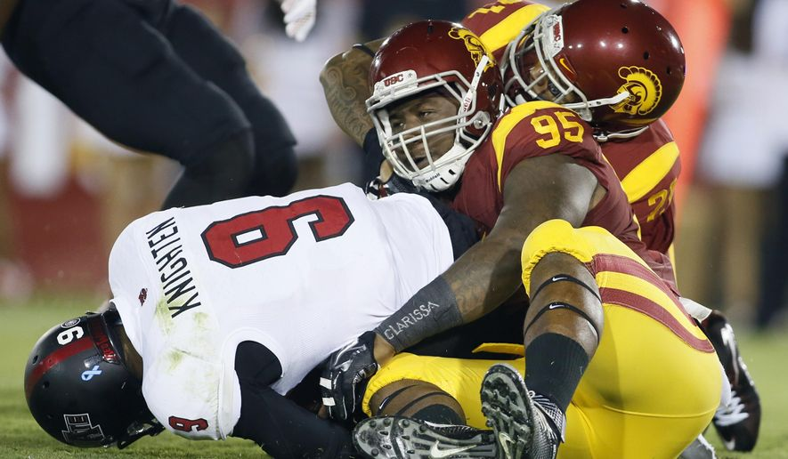Southern California defensive tackle Kenny Bigelow (95) and linebacker Su'a Cravens, back, sack Arkansas State quarterback Fredi Knighten during the first half of an NCAA college football game, Saturday, Sept. 5, 2015, in Los Angeles. (AP Photo/Danny Moloshok)