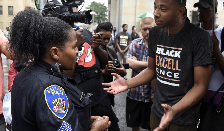 Sgt. K. Glanville of the Baltimore Police, left, talks with Kwame Rose, right, during a protest outside the Baltimore Circuit Court on Thursday, Sept. 10, 2015 in Baltimore.  The trials for six police officers charged in the arrest and death of Freddie Gray will be held in Baltimore, Circuit Court Judge Barry Williams ruled, saying it would be nearly impossible to find a place not inundated by publicity about the high-profile.  (Barbara Haddock Taylor/The Baltimore Sun via AP)  WASHINGTON EXAMINER OUT; MANDATORY CREDIT