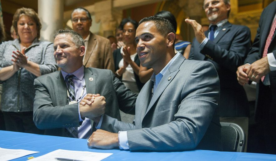 Kevin Brown, left, Chairman of the Mohegan Tribal Council and Rodney Butler, right, chairman of the Mashantucket Pequot Tribal Council, host an historic signing ceremony, Thursday, Sept. 10, 2015, at the state Capitol in Hartford, Conn., formalizing their new casino venture north of the city. In an effort to halt an exodus of gamblers and the loss of industry jobs, the tribes, backed by the legislature and Gov. Dannel P. Malloy, hope to compete with the planned MGM Resorts casino in Springfield, Mass. (Lauren Schneiderman/Hartford Courant via AP) MANDATORY CREDIT