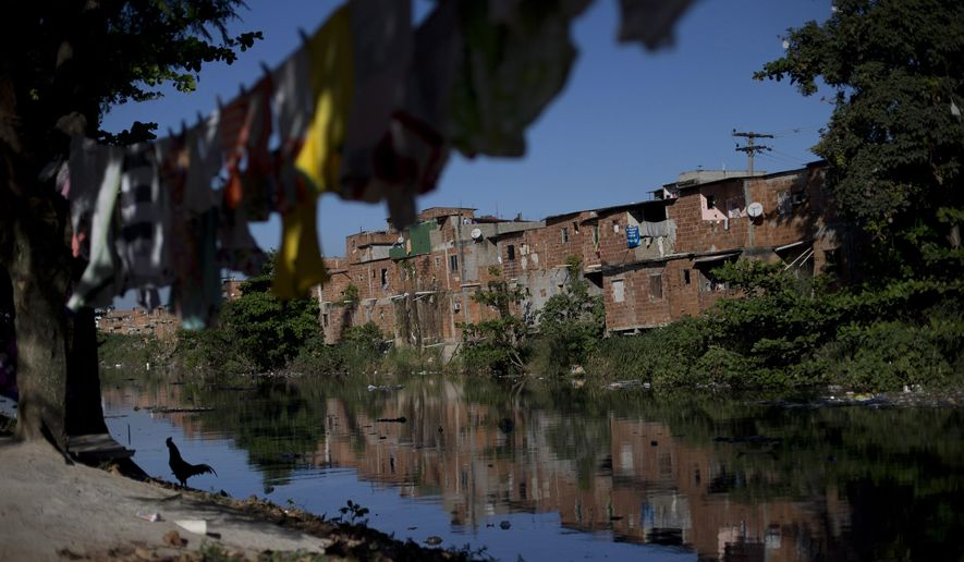 In this Aug. 13, 2015 photo, homes line the banks of an open-air ditch in the Mandela slum of Rio de Janeiro, Brazil. Mandela is a slum between two sewage-blackened rivers that flow into nearby Guanabara Bay where some Olympic water sports will be held in 2016. (AP Photo/Silvia Izquierdo)