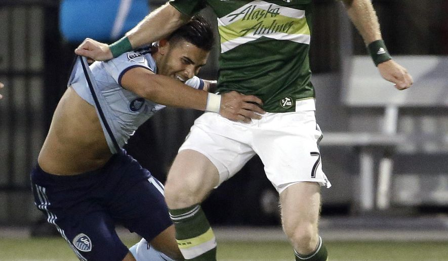 Sporting Kansas City forward Dom Dwyer, left, battles for the ball with Portland Timbers defender Nat Borchers during the first half of an MLS soccer match in Portland, Ore., Wednesday, Sept. 9, 2015. (AP Photo/Don Ryan)
