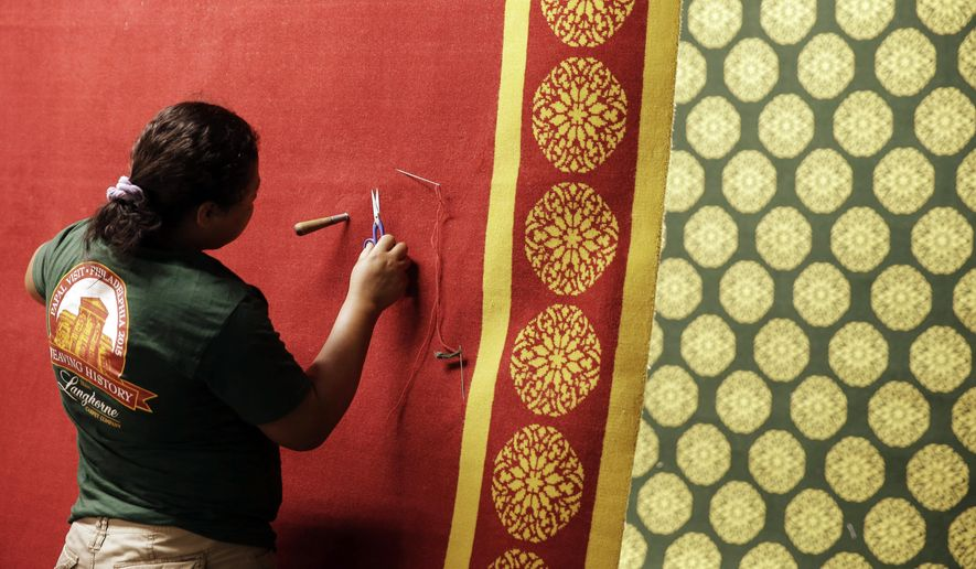 Burler Carmen Martinez works on a carpet made for Pope Francis' scheduled visit to Philadelphia, Thursday, Sept. 10, 2015, at the Langhorne Carpet Company in Penndel, Pa.  It features a gold border with a medallion design inspired by stained glass windows in the city's cathedral. (AP Photo/Matt Rourke)