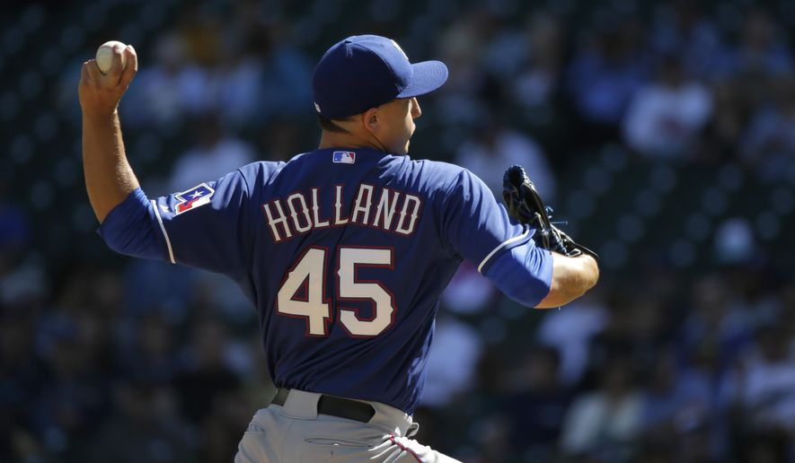 Texas Rangers starting pitcher Derek Holland throws against the Seattle Mariners in the first inning of a baseball game, Thursday, Sept. 10, 2015, in Seattle. (AP Photo/Ted S. Warren)