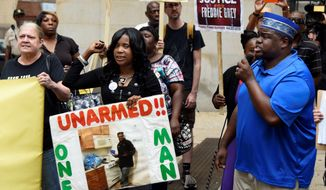 Tawanda Jones, center, and C.D. Witherspoon, right, chant at a rally with members of the Peoples Power Assembly outside the courthouse at Calvert and Lexington streets in Baltimore during court proceedings Thursday, Sept. 10, 2015, in the Freddie Gray case. (Barbara Haddock Taylor/Baltimore Sun via AP)